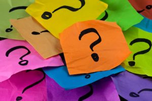 questions, decision making or uncertainty concept - a pile of colorful crumpled sticky notes with question marks