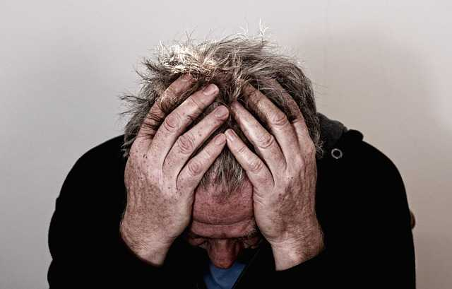 stress and burnout in business - man holding his head