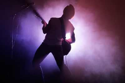 rockstar - man playing guitar on stage
